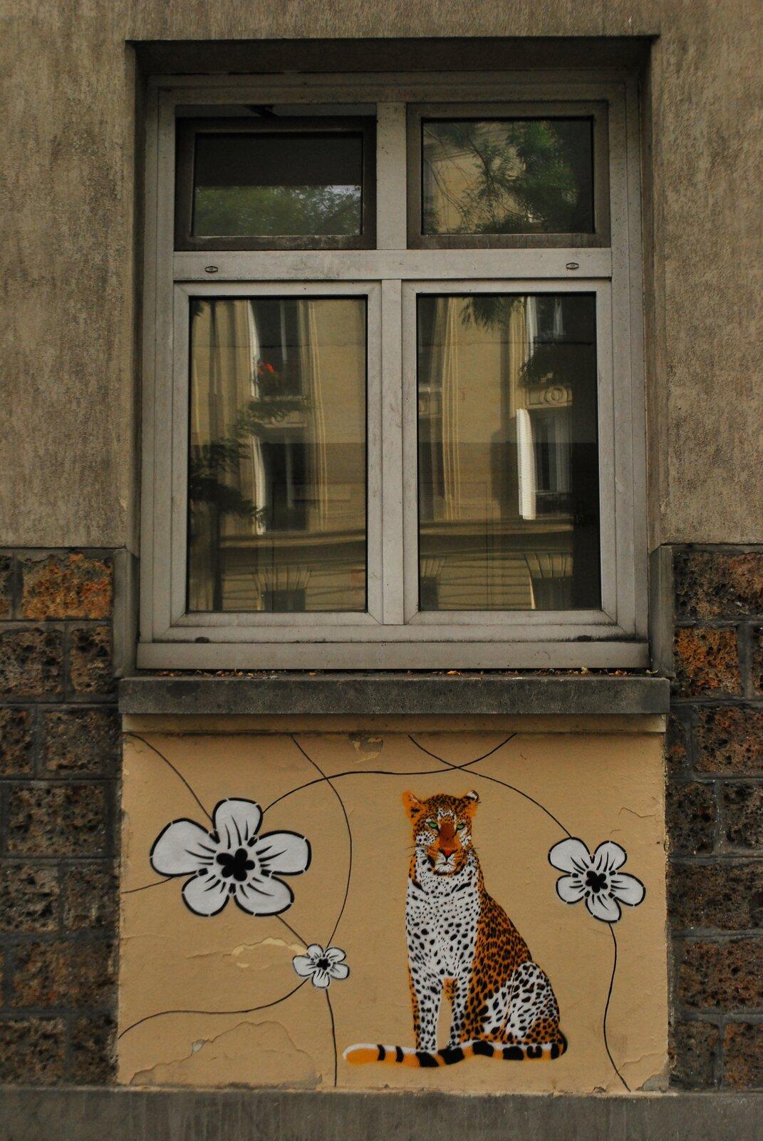Ilustracja przedstawia mural Mosko et Associes. Ukazuje wydzielony pod oknem żółty kwadrat, na którym namalowany jest siedzący tygrys oraz białe kwiaty na czarnych, wijących się łodygach.
