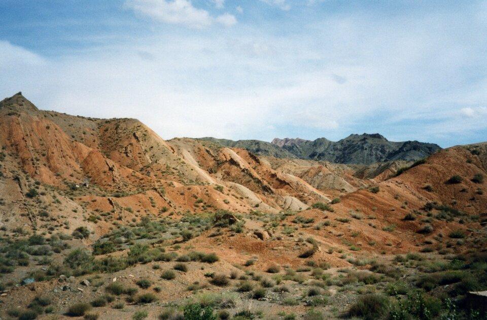 Na zdjęciu górzysty obszar, ceglasta ziemia porośnięta rzadkimi kępami traw.