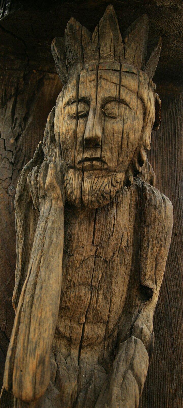 """Ilustracja przedstawia drewnianą rzeźbę """"Chrystusa frasobliwego"""". Ukazuje Jezusa zzamkniętymi oczami. Na głowie ma koronę. Jest ukazany wpozycji siedzącej, prawą ręką podpiera głowę."""