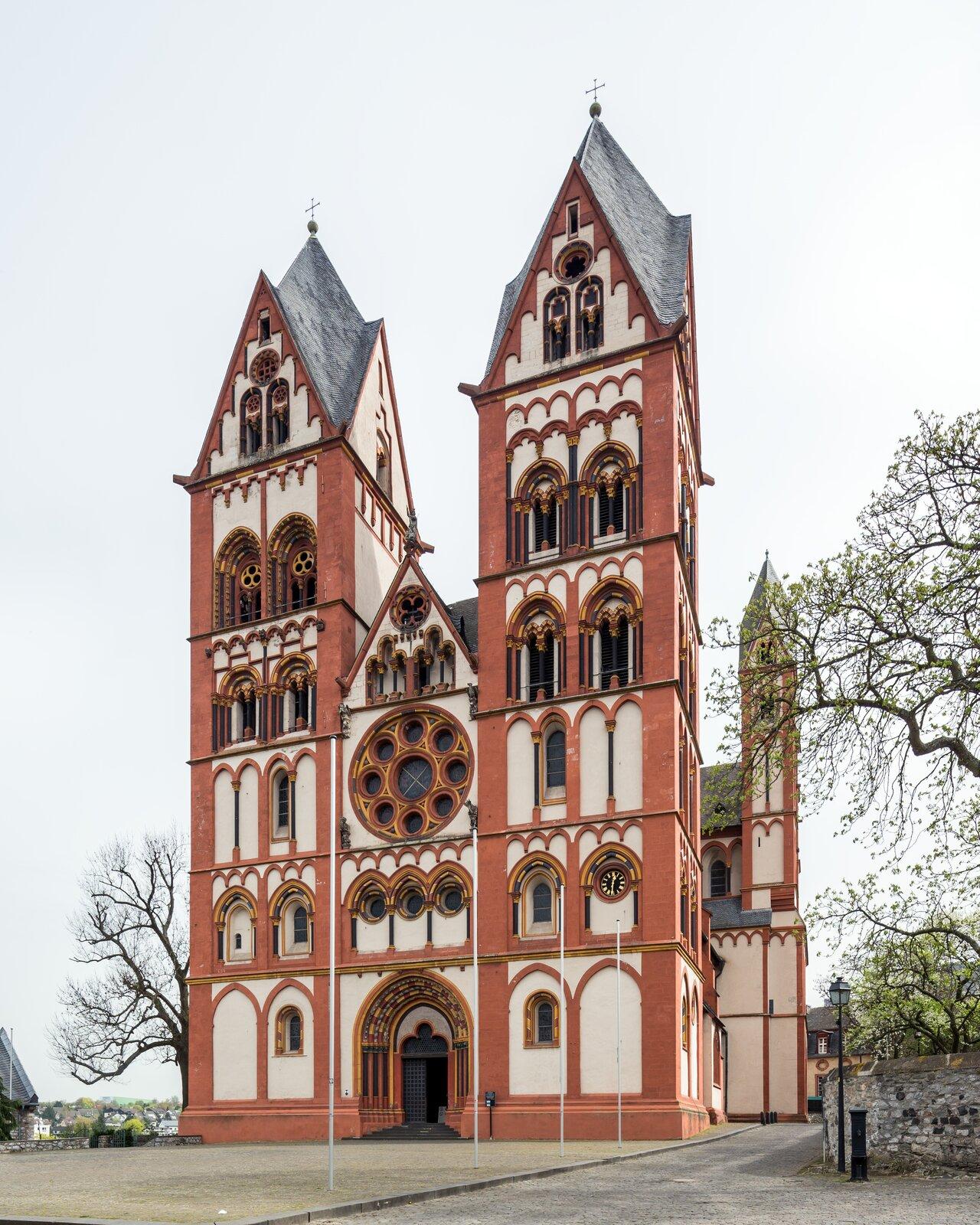 Ilustracja okształcie pionowego prostokąta przedstawia katedrę wLimburgu. Na zdjęciu został przedstawiony widok od strony portalu wejściowego. Katedra jest trójnawową budowlą zdwiema wieżami usytuowanymi wportalach bocznych. Na wszystkich kondygnacjach dzielonych gzymsem, znajdują się okna. Nad głównym wejściem usytuowana jest  rozeta oraz trójkątny szczyt.  Każda strona wieży zakończona jest wimpergą.