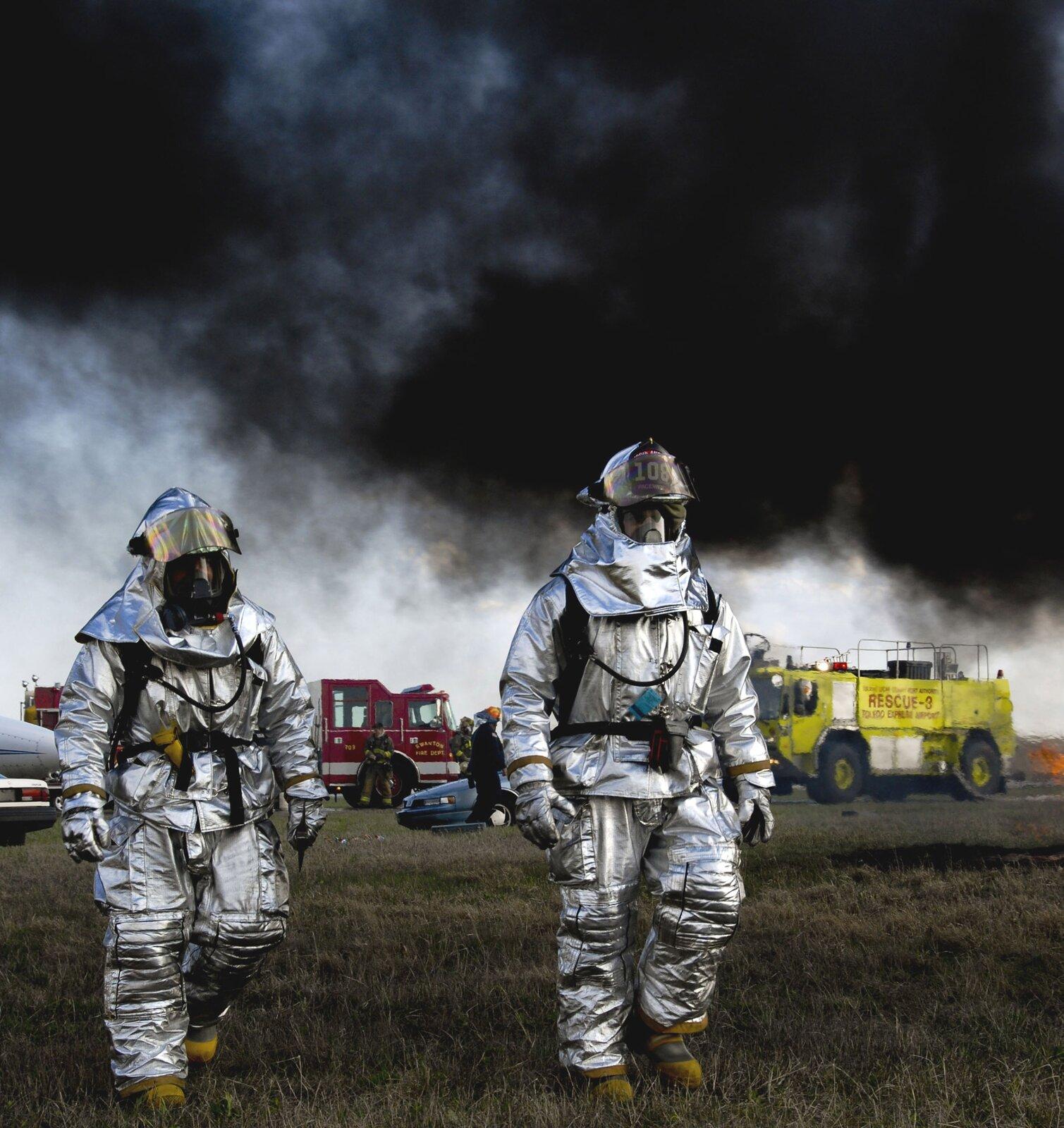 Zdjęcie przedstawia dwóch mężczyzn wskafandrach. Mężczyźni idą po trawie. Wtle wozy strażackie. Niebo pokryte gęstym, czarnym dymem. Skafandry ikaski srebrno-szare. Skafandry osłaniają całe ciała mężczyzn. Mężczyźni na nogach mają żółte buty.