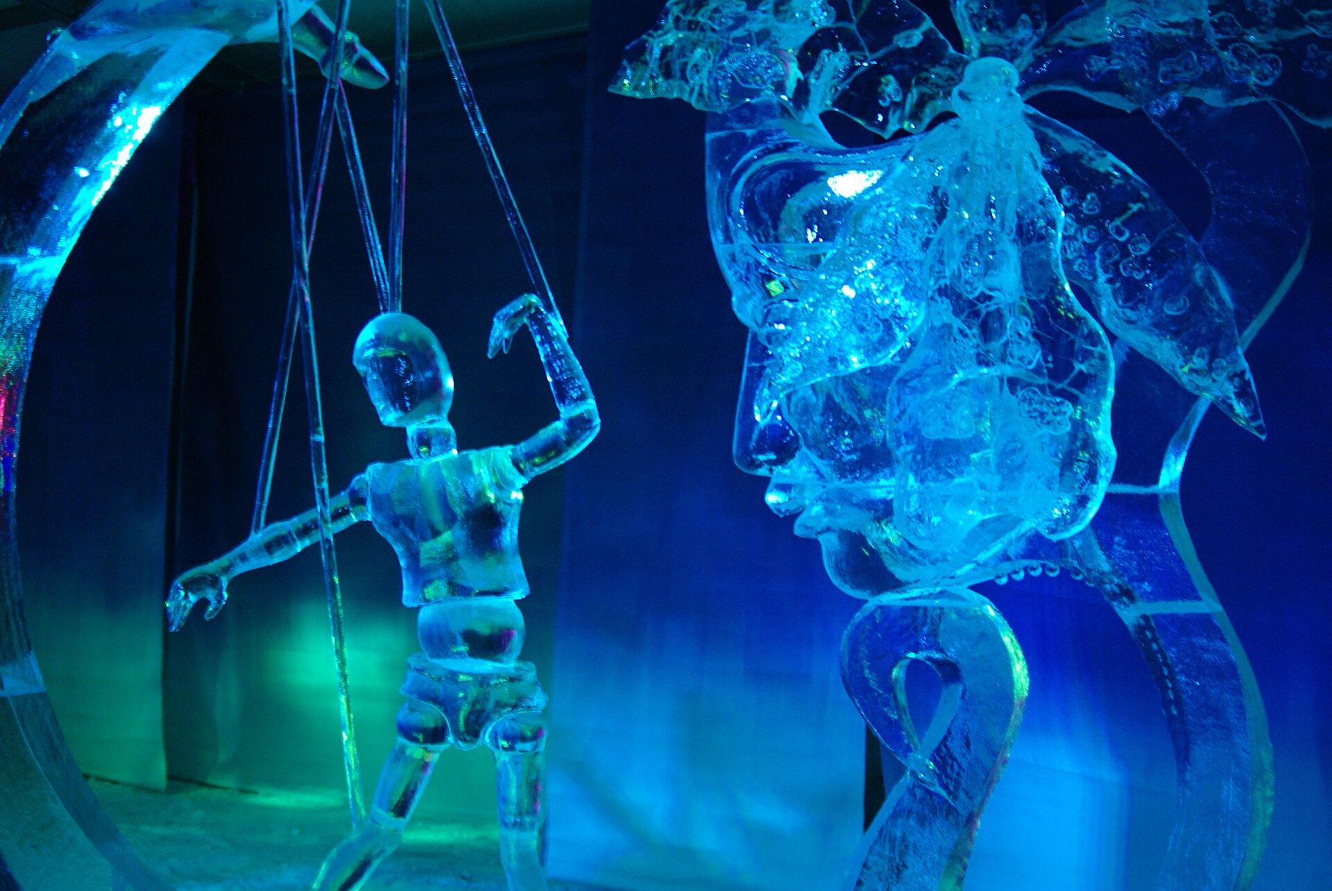 Ilustracja przedstawia rzeźby wykonane zlodu. Zlewej strony znajduje się rzeźba kukiełki na sznurkach, apo prawej stronie rzeźba twarzy. Wpomieszczeniu, wktórym prezentowane są rzeźby oświetlenie jest niebieskie izielone. Taki sam kolor mają rzeźby.