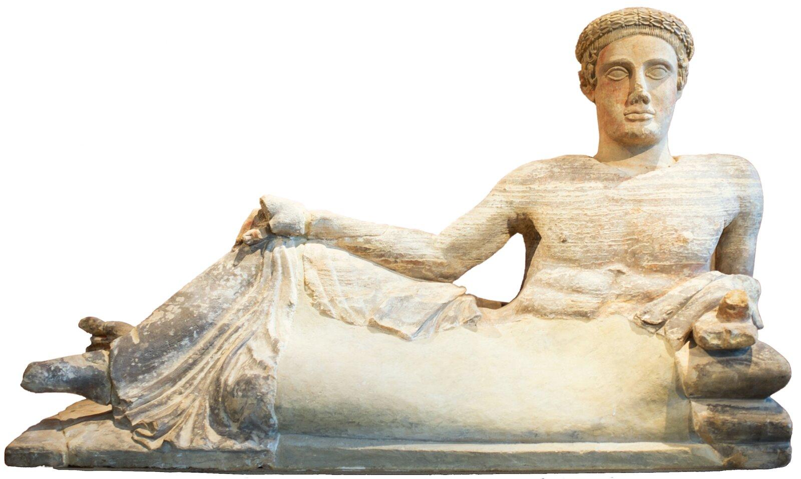 - Rzeźba przedstawiająca mężczyznę wpozycji pół leżącej na lewym boku. Na głowie ma okrągłą czapkę, ma nagi tors. Lewym łokciem wspiera się na poduszkach, prawą rękę trzyma na prawym kolanie.
