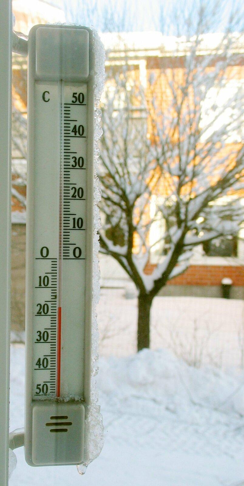 Fotografia przedstawia termometr, który umocowany jest po zewnętrznej stronie okna. Termometr okienny służy do pomiaru temperatury powietrza. Zimowy krajobraz za oknem wskazuje, że temperatura może być niska. Ztermometru można odczytać, że temperatura wynosi około -17°C.