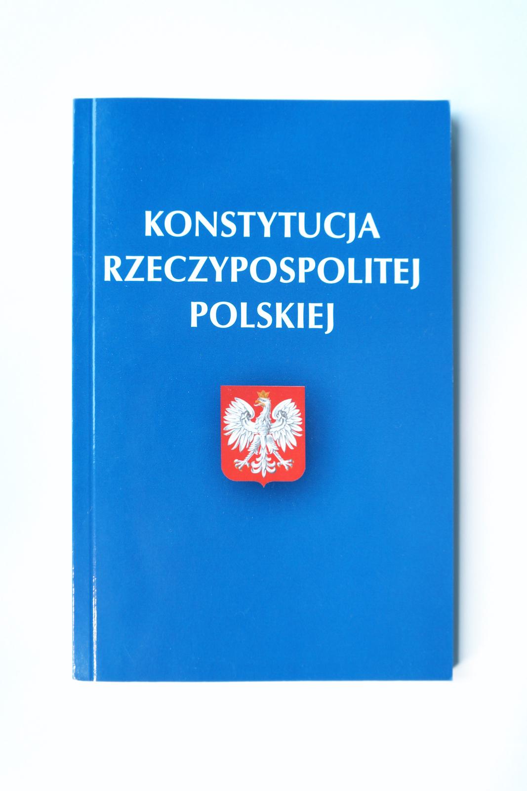 Ilustracja przedstawia prostokątną okładkę książki, na której umieszczono biały napis Konstytucja Rzeczypospolitej Polskiej. Poniżej godło Polski – biały orzeł na czerwonym tle. Głowa orła skierowana jest wprawo.