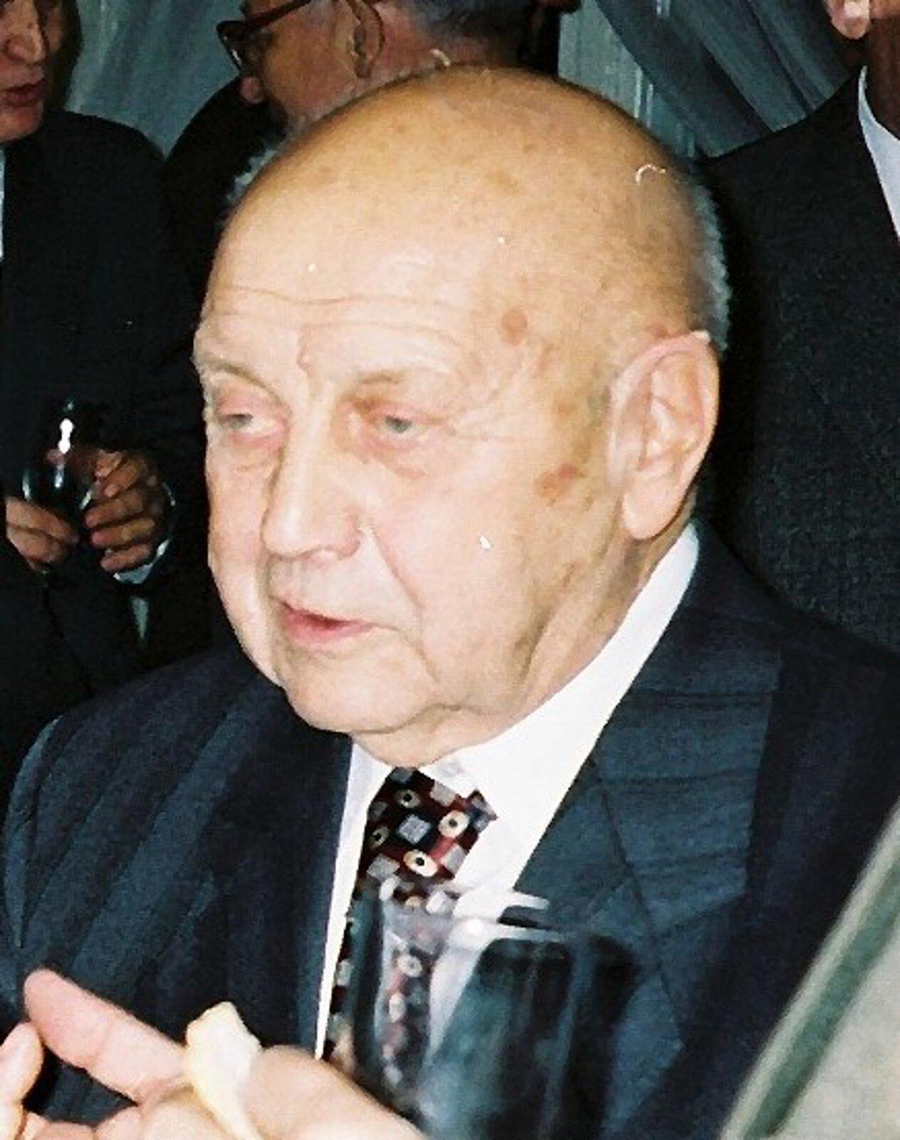 Na zdjęciu popiersie starszego mężczyzna zdużą łysiną. Ubrany wgarnitut ikrawat.