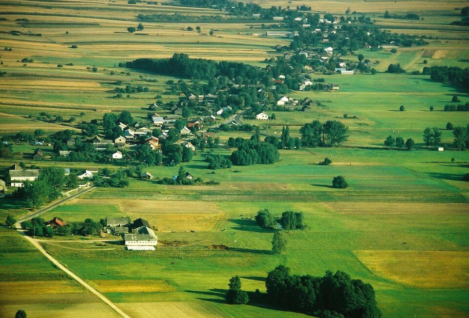 Na zdjęciu lotniczym rozległe tereny zielone, łąki ipola uprawne. Środkiem biegnie droga, przy której są domy idrzewa.