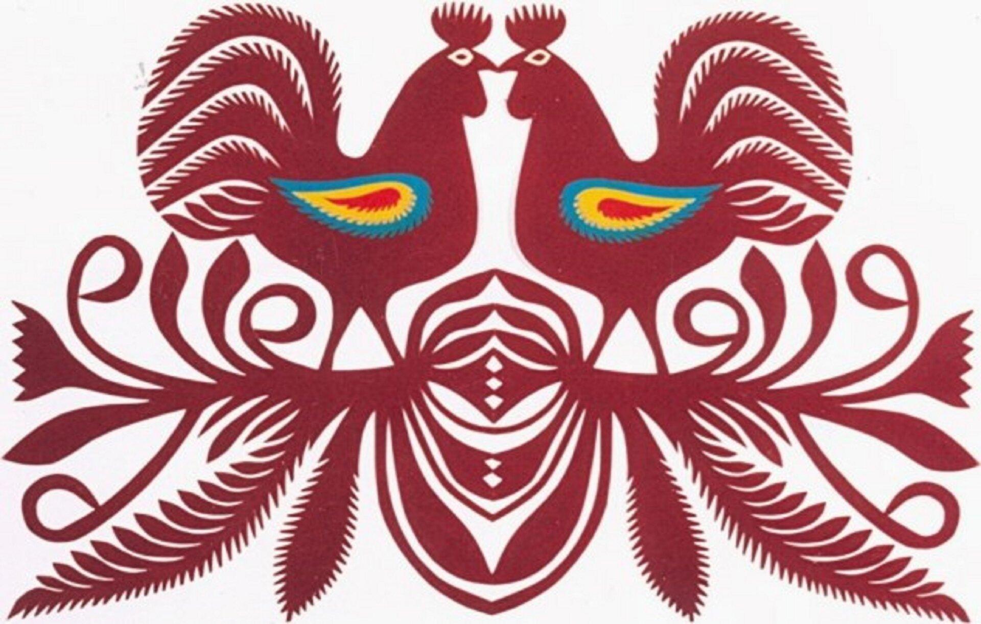 Ilustracja przedstawia wzór kurpiowskich kogutów. Są to dwa koguty stojące na gałązce istykające się dziobami. Całość jest wkolorze bordowym za wyjątkiem skrzydeł kogutów, które mają barwę niebieską, żółtą iczerwoną. Od gałązki odchodzą różnego rodzaju listki.