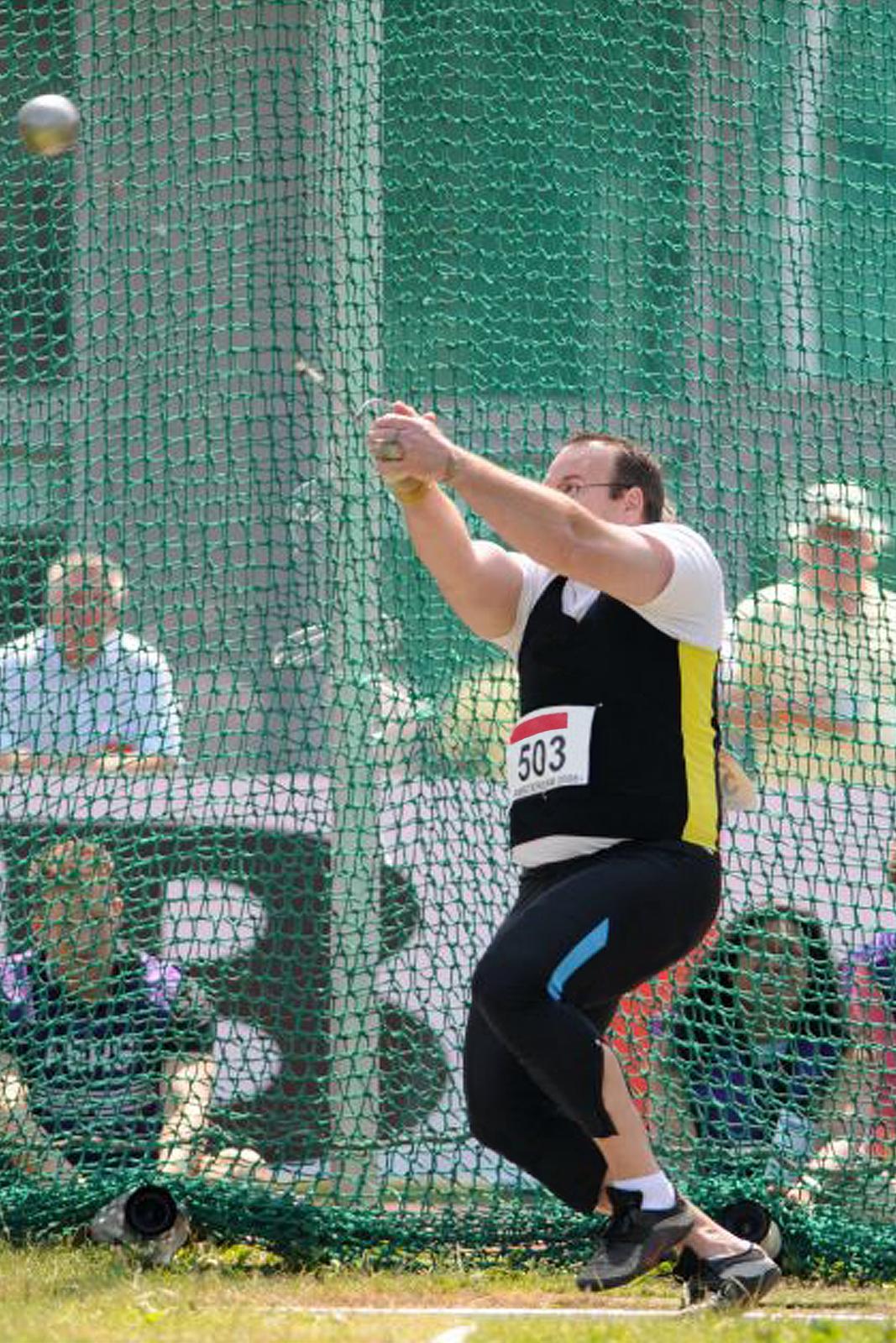 Zdjęcie przedstawia sportowca podczas rzutu młotem. Na pierwszym planie mężczyzna wwieku ok. 35 lat. Mężczyzna jest ubrany wstrój sportowy. Wtle widoczna zielona siatka ochronna.