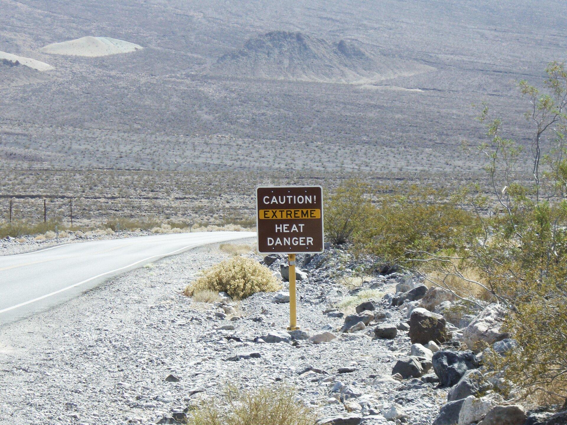 Fotografia przedstawia tablicę, informująca ozagrożeniu nadzwyczaj wysoką temperaturą powietrza. Tablica jest prostokątna, czerwona, zbiałymi iżółtymi napisami wjęzyku angielskim. Stoi na skraju Doliny Śmierci na pustyni Mojave. Przy żółtym słupie tablicy leżą szare ibrązowe kamienie, między którymi rosną kępy roślin – traw iniskich krzewów. Wtle łańcuchy górskie.