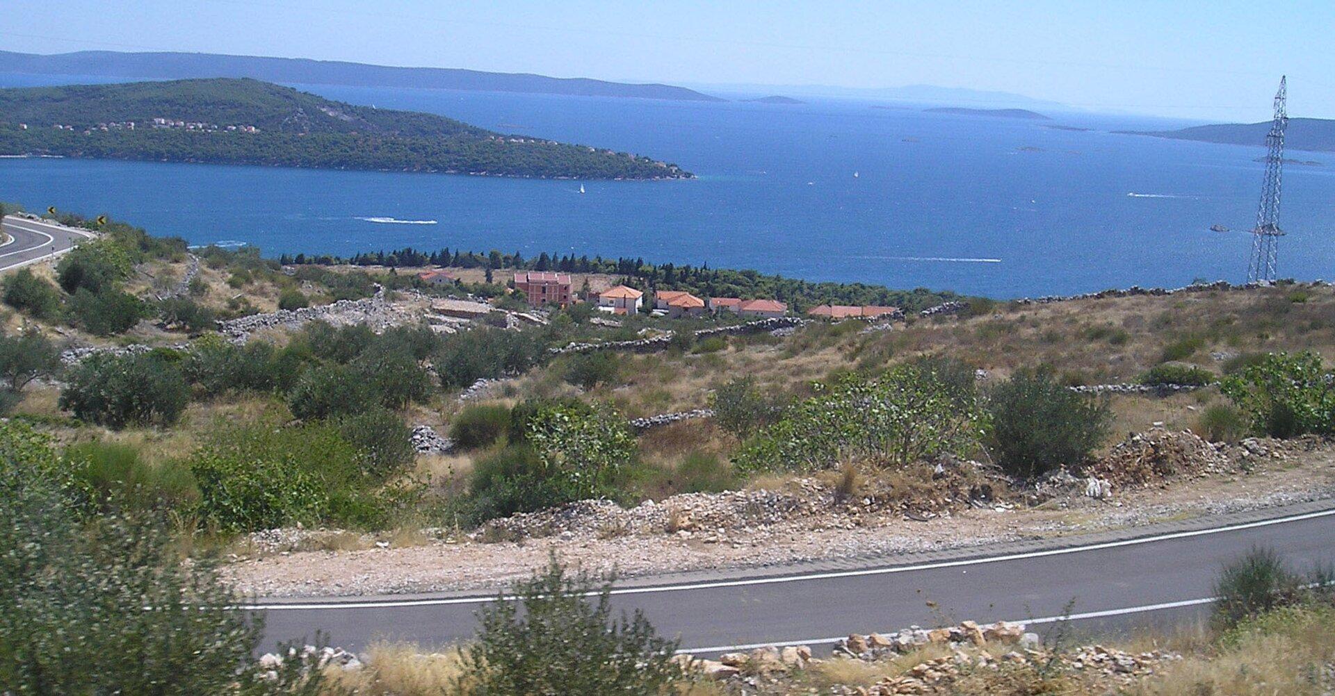 Na zdjęciu morze otoczone łagodnymi górami. Podłużna zalesiona wyspa położona równolegle do brzegu. Na pierwszym planie zabudowania, jasne domy zczerwonymi dachami wśród bujnej roślinności.