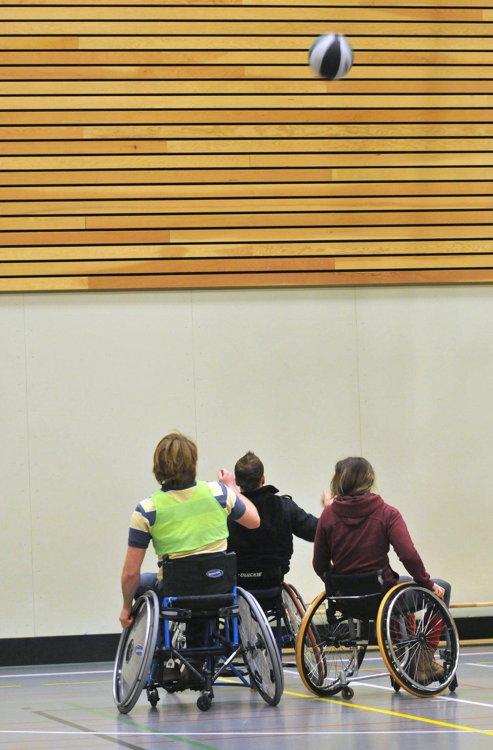 Fotografia przedstawia sytuację podczas meczu koszykówki rozgrywanego przez zawodników na wózkach inwalidzkich. Każdy ztrzech zawodników przedstawionych na zdjęciu spogląda za podrzuconą do góry piłką, trwając wgotowości do jej przechwycenia.