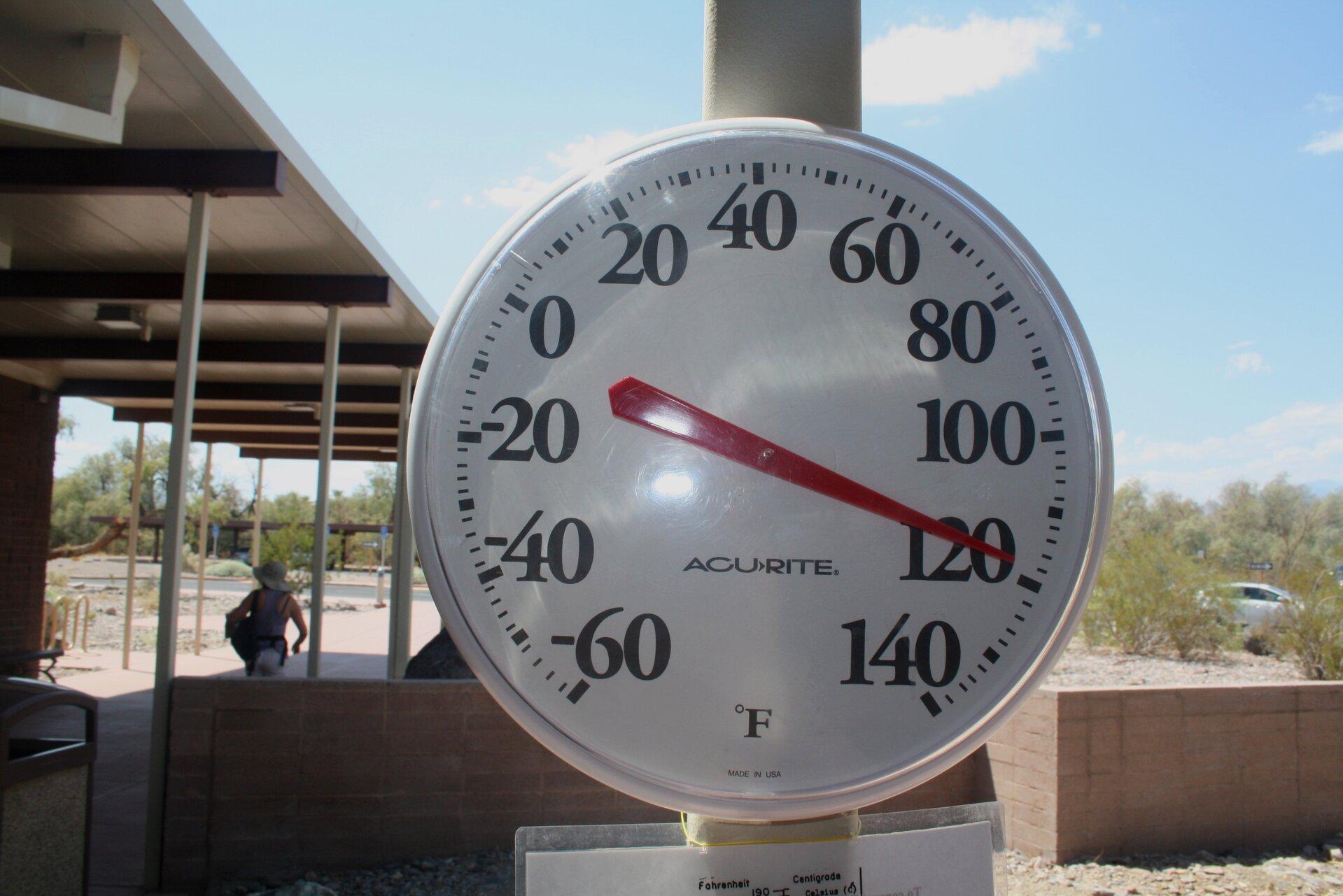 Na zdjęciu okrągły przyrząd zbiałą tarczą, podziałką iczerwoną wskazówką. To termometr. Wskazówka wskazuje wartość sto dwadzieścia stopni Fahrenheita. Wtle zlewej strony zabudowania. Zprawej strony krzewy.