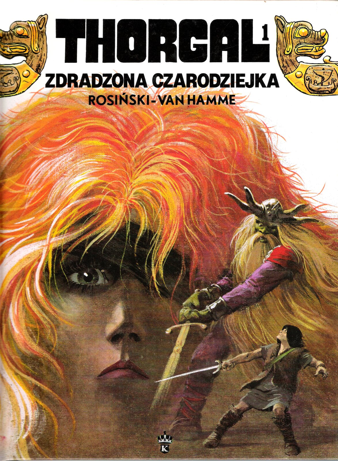 """Ilustracja przedstawia okładkę komiksu Jeana Vana Hamme'a """"Thorgal. Zdradzona czarodziejka"""", zaprojektowaną przez Grzegorza Rosińskiego. Okładka przedstawia twarz rudowłosej dziewczyny idwie mniejsze, walczące zsobą na miecze postacie. Udołu znajduje się czarnowłosy wojownik zmieczem wprawej dłoni. Głowę ma podniesioną na większego od siebie wikinga ozielonej twarzy iubranego whełm zrogami. Wiking trzyma swój miecz oburącz. Ma długie włosy ibrodę do pasa. Groźnym wzrokiem spogląda na przeciwnika. Wgórnej części okładki znajduje się tytuł inazwisko autora. Po bokach napisy dekorowane są głowami smoków."""