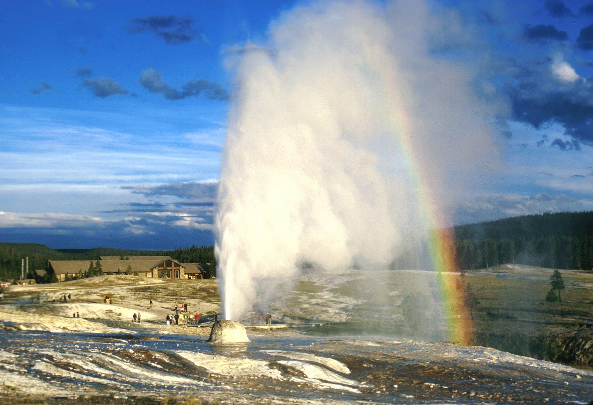 Fotografia przedstawia tryskający wodą gejzer wParku Narodowym Yellowstone. Zboku wkropach wody utworzyła się tęcza. Gejzer to wypukłość na szaro – brązowo – białym podłożu. Wysokość wytrysku wody można ocenić, porównując ją zmalutkimi postaciami ludzi na dalszym planie. Wtle zabudowania ilas.