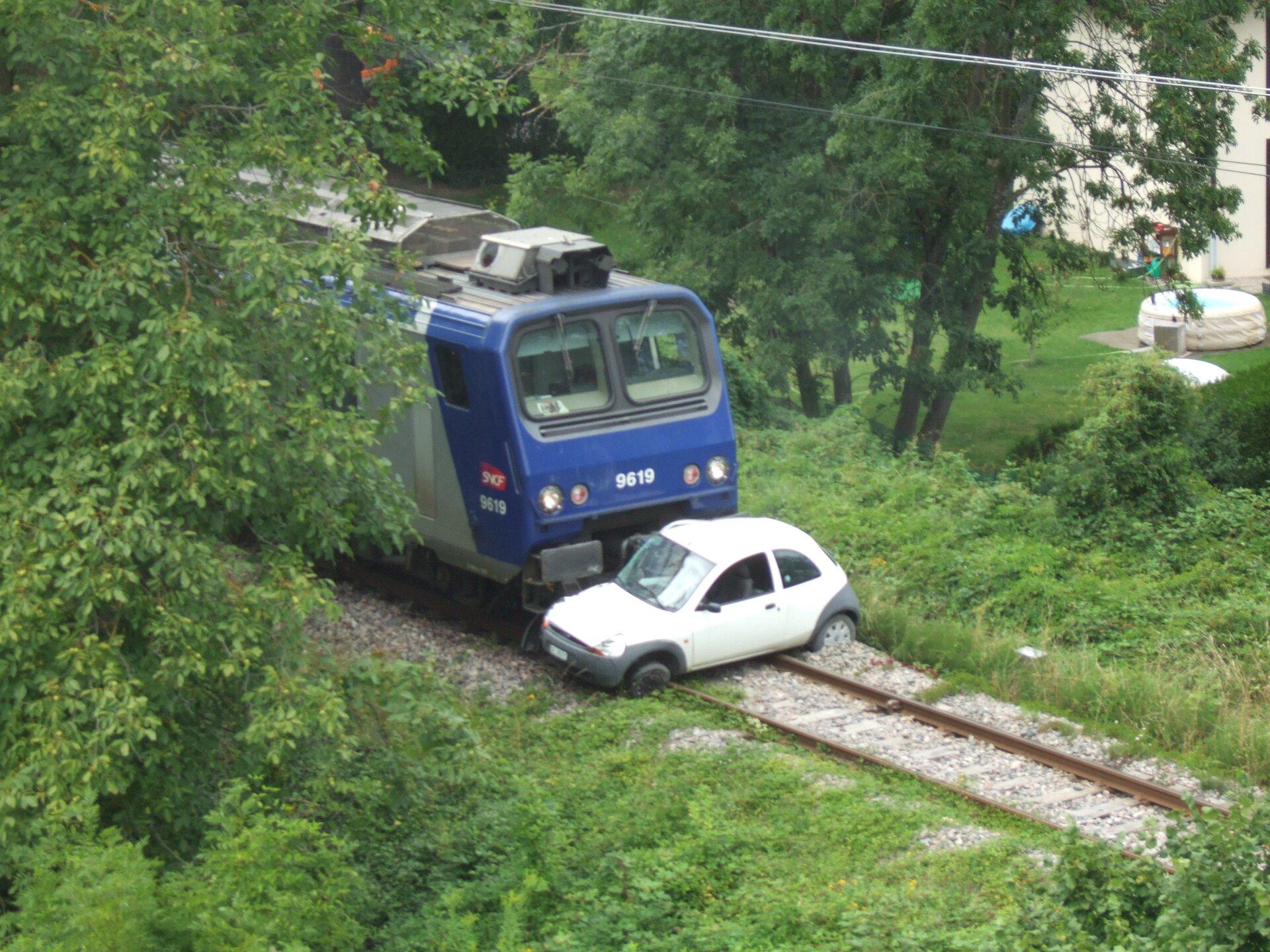 Zdjęcie przedstawia katastrofę kolejową. Na pierwszym planie teren porośnięty trawą, krzakami idrzewami. Na środku torowisko. Tory biegną zdolnego prawego rogu kadru wgórę, na lewo. Wpołowie torów stoi biały samochód osobowy uderzony ipchany przez odcinek co najmniej kilkunastu metrów przez niebiesko szarą lokomotywę. Lewe tylne koło samochodu zagłębione wkamienny podkład torów, lewe przednie opiera się otor.