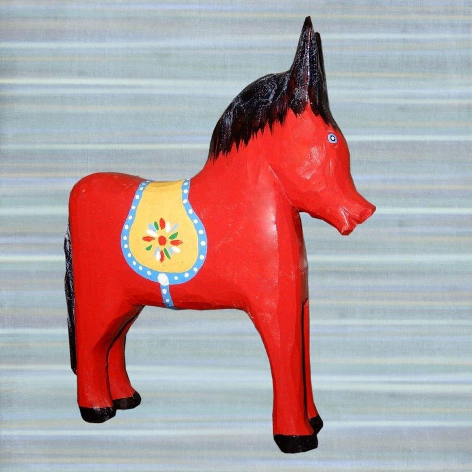 Ilustracja przedstawia zabawkowego konika wkolorze czerwonym. Konik ma czarną grzywę inamalowane żółte siodło ozdobione kolorowym kwiatkiem.