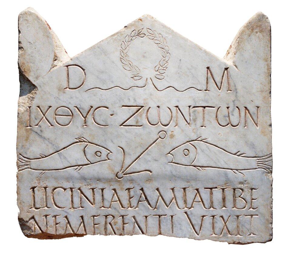 Na kamiennej tablicy wyryte są dwie ryby zwrócone do siebie pyskami, między nimi kotwica, anad nimi ipod nimi wyryte są litery napisów: