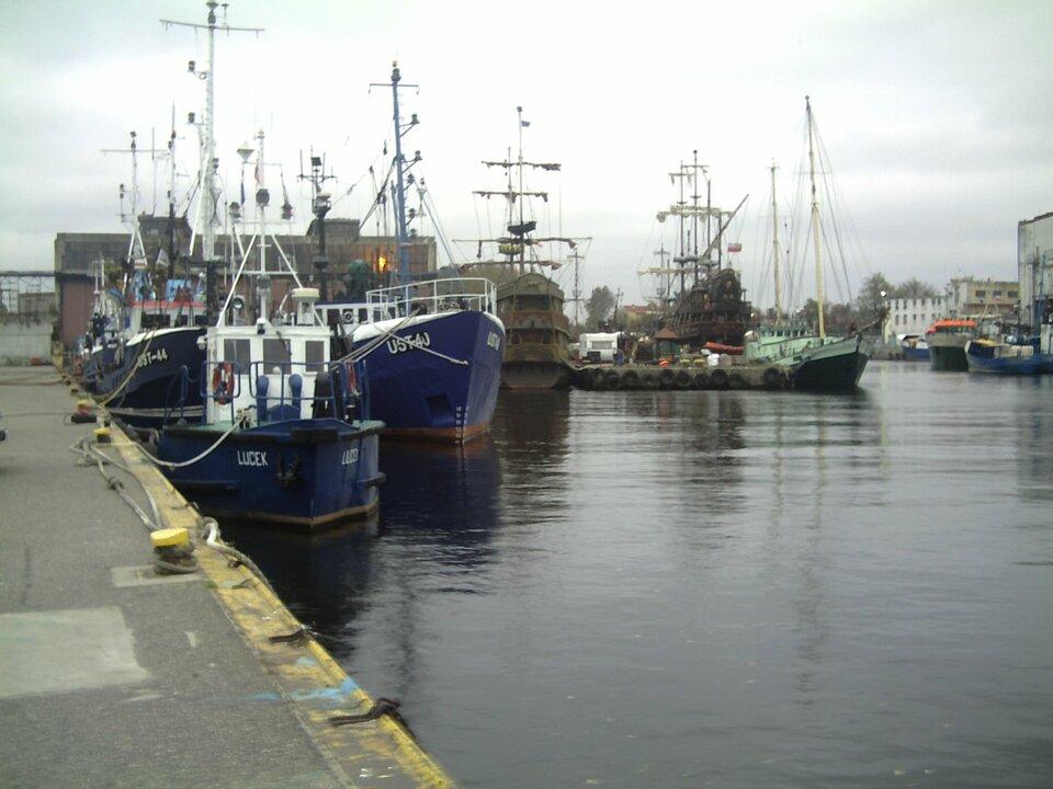 Na zdjęciu kilka kutrów rybackich zacumowanych przy betonowym nabrzeżu.