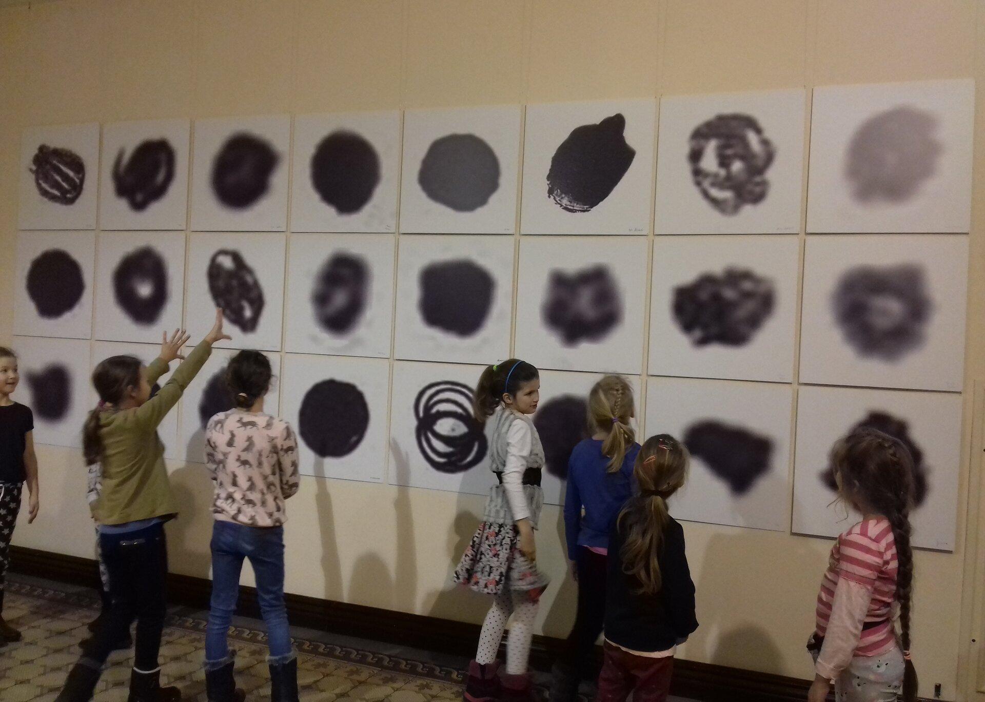 Ilustracja przedstawiająca dzieci oglądające wystawę sztuki.
