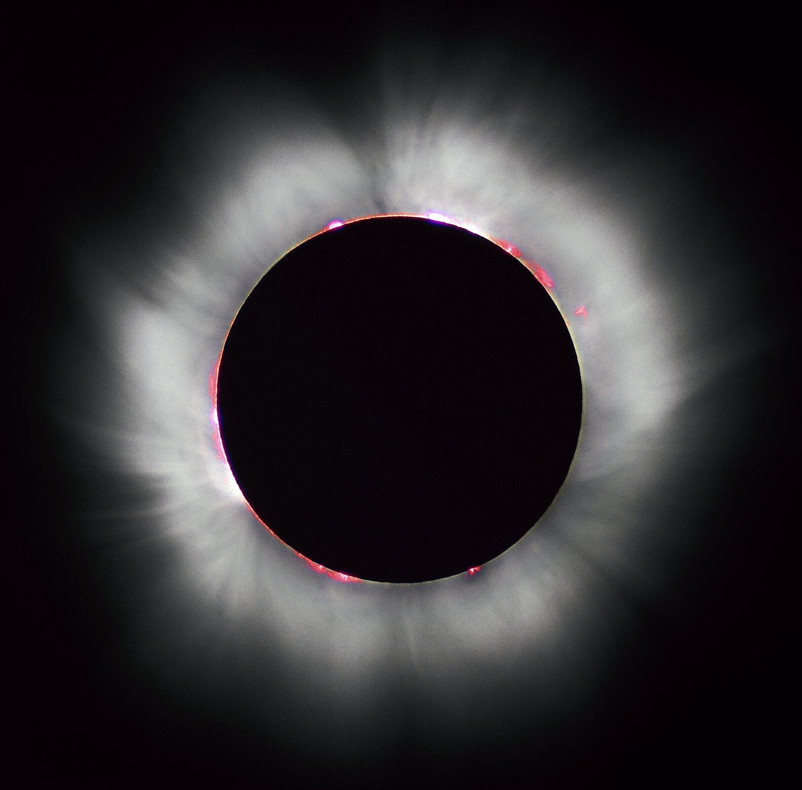 Zdjęcie przedstawia całkowite zaćmienie Słońca przez Księżyc w1999 roku we Francji. Tarcza słoneczna jest całkowicie przesłonięta całkowicie czarną tarczą Księżyca. Wyraźna jest korona słoneczna wpostaci białej poświaty przypominającej mgłę ikrańcowe obszary graniczne Słońca wpostaci czerwonych plam wokół tarczy Księżyca.