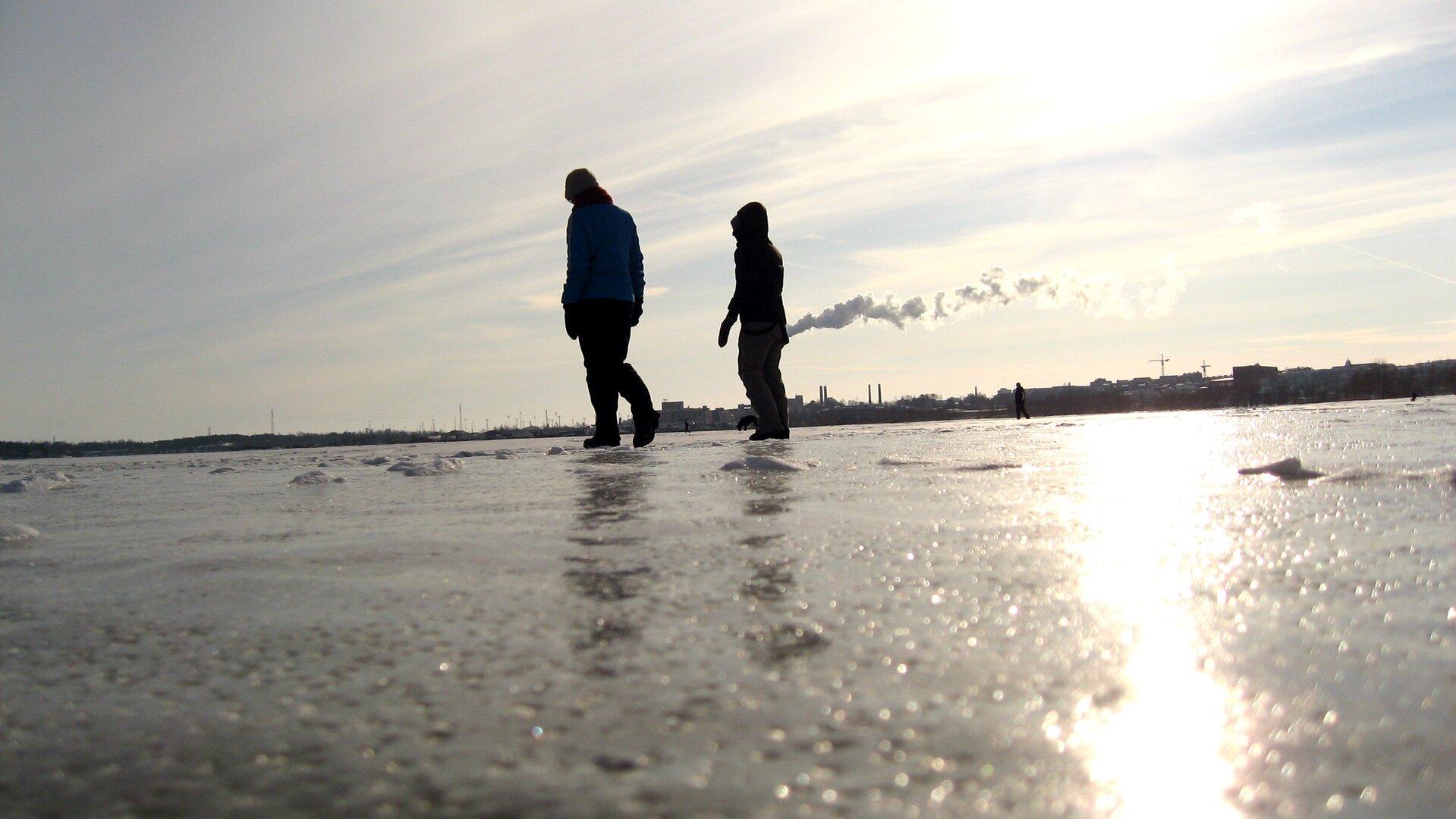 Kolorowe zdjęcia przedstawia dwie osoby spacerujące po lodzie. Słoneczny zimowy dzień. Dół zdjęcia to zamarznięta powierzchnia jeziora. Szarawy lód ochropowatej powierzchni. Na środku zdjęcia dwie osoby wciepłych ubraniach spacerują wlewo. Na linii horyzontu budynki miasta. Zkomina wydobywa się dym. Niebo szarawe.