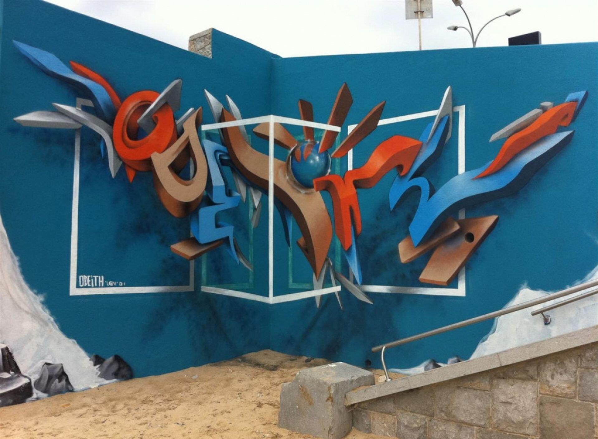 Ilustracja przedstawia graffiti Sergio Odeith'a. Ukazuje wielobarwny napis zamieszczony wrogu muru wtaki sposób, że tworzy efekt trójwymiarowy. Na ścianie ipodłodze został namalowany cień napisu. Dodatkowo wprowadzono biały kontur łamanej ściany składającej się zczterech części.