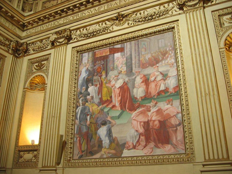 """Pius IV (1559-1565) – fresk wkaplicy kościoła Rzymskiego przedstawiający Piusa IV, który wydaje bullę """"Benedictus Deus"""", potwierdzającą dekrety soboru trydenckiego PiusIV (1559-1565) zaraz po wyborze odciął się od działań swojego poprzednika, zapowiedział reformy wKościele. Zaczął od pozbycia się nepotów poprzednika Pawła IV Carafy, ana najbliższego doradcę wyznaczył znanego zpobożności ireligijności późniejszego świętego Karola Boromeusza (swojego siostrzeńca, azatem to także był nepotyzm). Najważniejsze było jednak wznowienie zawieszonych obrad soboru trydenckiego idoprowadzenie jego obrad do szczęśliwego końca. Ostatnie sesje odbyły się 3 i4 grudnia 1563 r., a26 stycznia 1564 r. papież zatwierdził dokumenty, wtym wyznanie wiary. Wtym samym 1564 r. ogłoszono nowy """"Indeks Ksiąg Zakazanych"""". Papież zreformował też procedury wewnętrzne Kurii – m.in. dotyczące konklawe.Prezentowany fresk (1588) autorstwa Pasquale Cati znajduje się wkaplicy Altempsów wbazylice Najświętszej Marii Panny na Zatybrzu wRzymie. Źródło: Torvindus, Pius IV (1559-1565) – fresk wkaplicy kościoła Rzymskiego przedstawiający Piusa IV, który wydaje bullę """"Benedictus Deus"""", potwierdzającą dekrety soboru trydenckiego, 2004, fresk, licencja: CC BY-SA 3.0."""