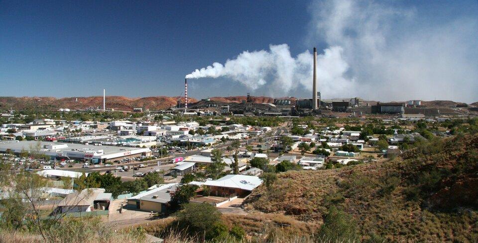Na zdjęciu teren zabudowany. Na pierwszym planie domy mieszkalne ihale fabryczne. Wtle zabudowania przemysłowe, wysokie kominy. Zkomina wydobywa się dym.