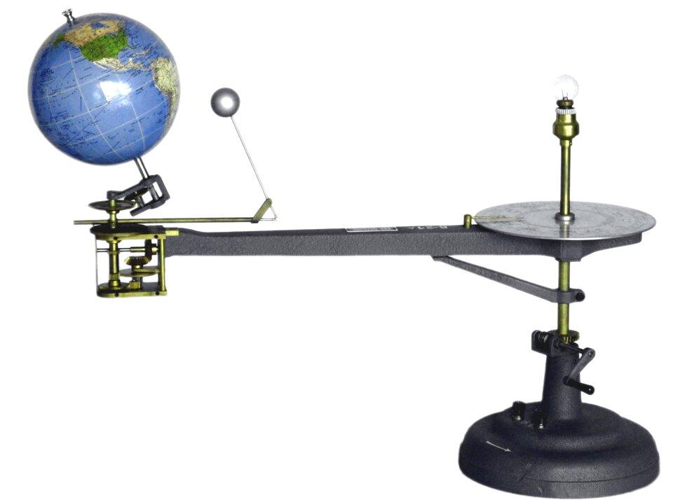 Zdjęcie przedstawia model do prezentacji ruchu Ziemi iKsiężyca względem siebie oraz względem Słońca. Główna część modelu to podstawka po prawej stronie zdjęcia. Na pionowej osi, przymocowanej do podstawki, umocowano metalowe ramię wpoziomie. Metalowe ramię skierowane wlewą stronę. Na końcu ramienia umieszczona kula ziemska. Kula ziemska nachylona wlewo. Na prawo od kuli ziemskiej mała srebrna kula. To Księżyc. Zarówno kula ziemska, jak iKsiężyc mogą się swobodnie obracać wokół własnej osi oraz wokół Słońca. Księżyc dodatkowo może krążyć wokół Ziemi.