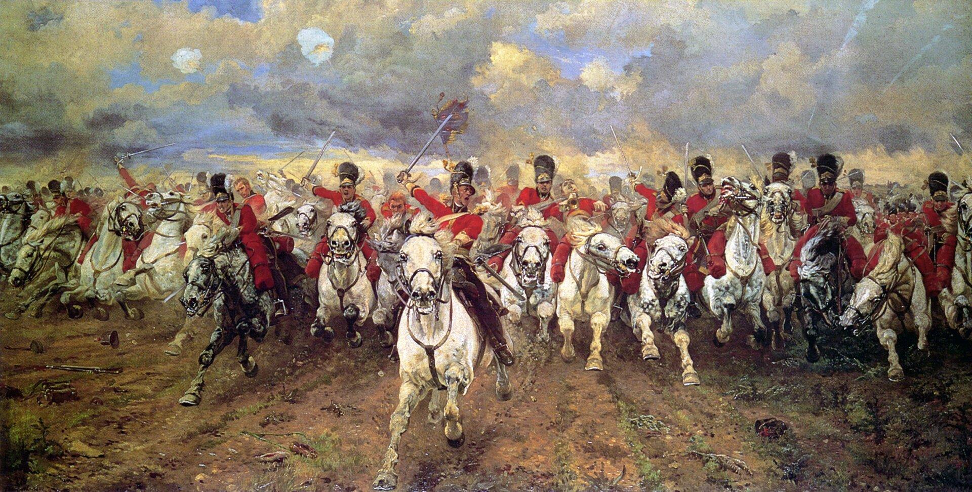 """Ilustracja przedstawia dzieło Elizabeth Thompson """"Scotland Forever!"""". Obraz ukazuje szarżę Królewskiego Szkockiego Szaraka , brytyjskiego pułku kawalerii, który szarżował uboku brytyjskiej ciężkiej kawalerii wbitwie pod Waterloo w1815 roku. Konie, które dominują na zdjęciu, to ciężkie wierzchowce. Galopują prowadzone przez żołnierzy wczerwonych mundurach. Malarka ujęła scenę perspektywicznie, co potęguje wrażenie pędu. Nad pędzącym wojskiem unosi się niebo zżółto-szarymi chmurami."""