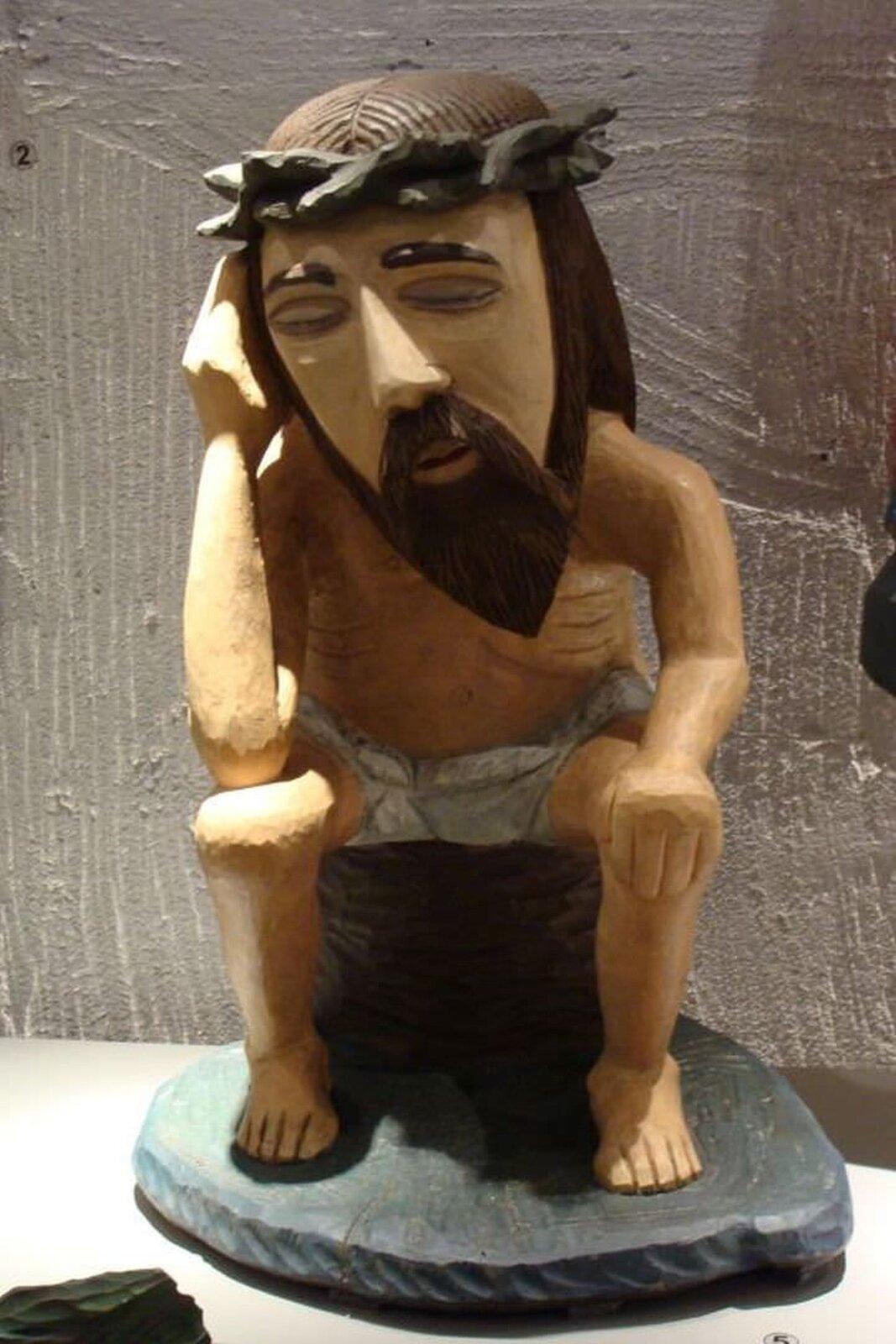 """Ilustracja przedstawia drewnianą rzeźbę Konstantego Marcinkowskiego """"Chrystus frasobliwy"""". Ukazuje Jezusa zzamkniętymi oczami. Na głowie ma koronę cierniową. Jest ukazany wpozycji siedzącej, prawą ręką podpiera głowę."""