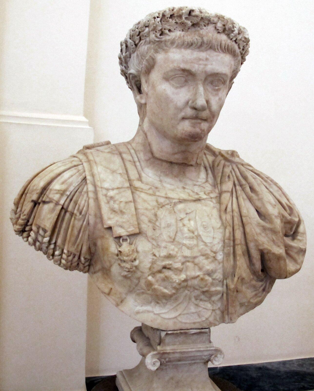Ilustracja przedstawia marmurowe popiersie cesarza Tyberiusza. Władca ukazany jest jako młody człowiek. Ma krótkie ufryzowane włosy idrobne usta. Na szatę założoną ma bogato rzeźbioną zbroję. Popiersie przedstawione jest bez rąk. Jest ustawione na cokole wformie głowicy kolumny jońskiej.