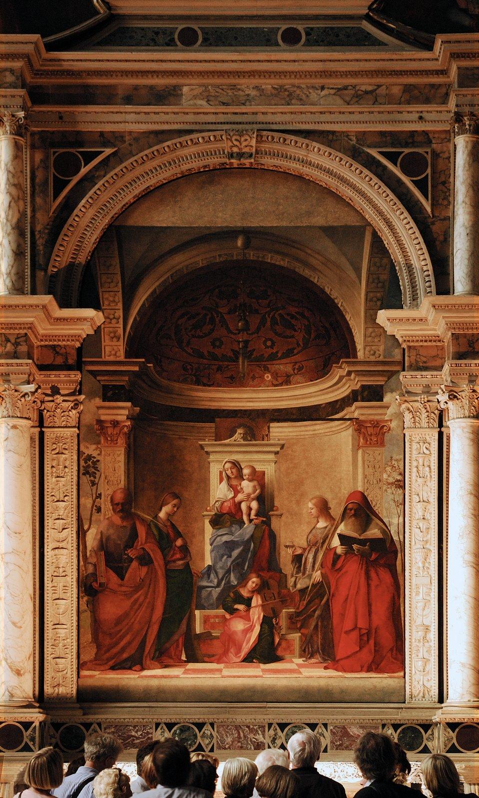 """Obrazz1505 r. weneckiego malarza B. Belliniego """"Święta rozmowa"""" (Sacra conversatione) zkościoła wWenecji. Obrazz1505 r. weneckiego malarza B. Belliniego """"Święta rozmowa"""" (Sacra conversatione) zkościoła wWenecji. Źródło: Giovanni Bellini, Roman Bonnefoy, 1505, Wikimedia Commons, licencja: CC BY-SA 3.0."""