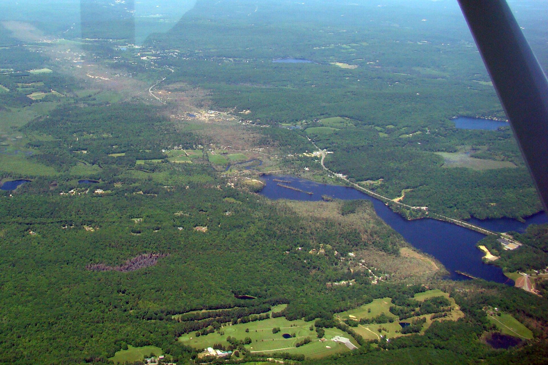 Zdjęcie przedstawia skutki przejścia trąby powietrznej nad terenem zalesionym. Od lewej strony do prawej górnej części zdjęcia przebiega szeroki pas powalonych drzew. Po obu stronach pasa znajduje się nienaruszony las.