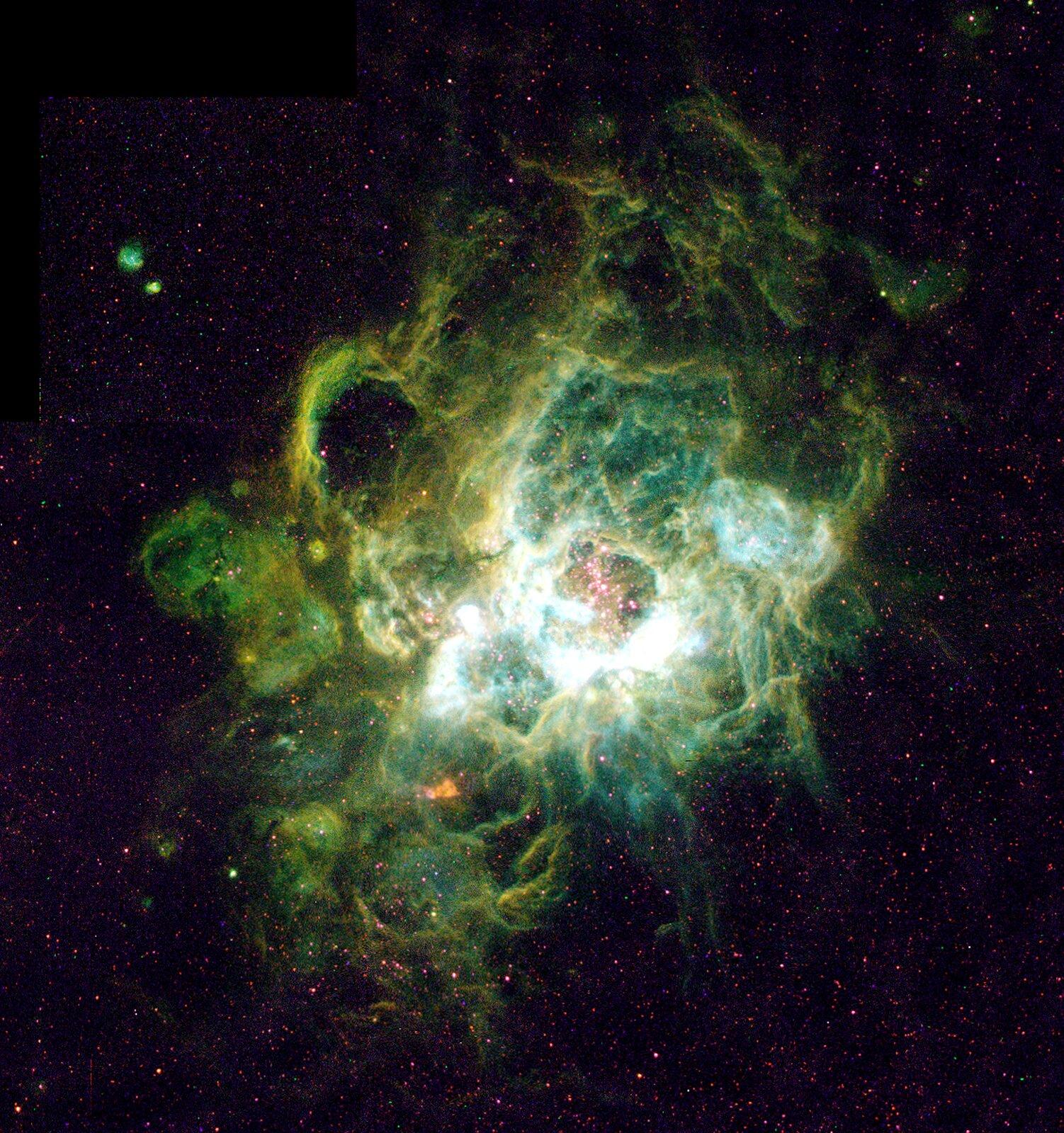 Grafika przedstawia mgławicę gazową wgwiazdozbiorze trójkąta. Tło czarne. Mgławica wygląda jak obłoki wkolorach od morsko-zielonego, poprzez seledynowy aż do prawie białego.