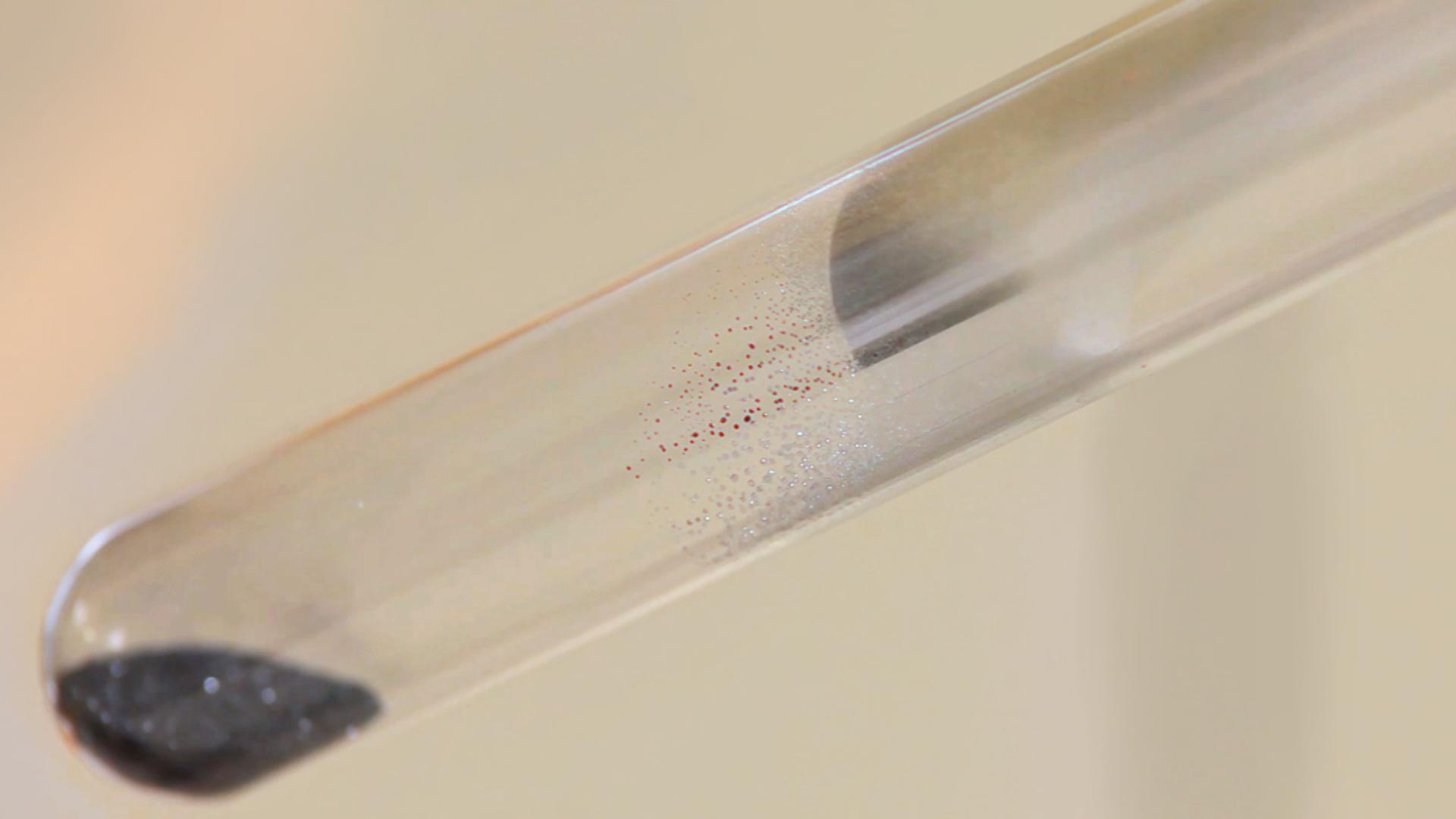 Zdjęcie zestawu do rozkładu tlenku rtęci(II) podczas pracy. Na zdjęciu widać rtęć osadzającą się wpostaci maleńkich kropelek na ściankach probówki powyżej ogrzewanego HgO.