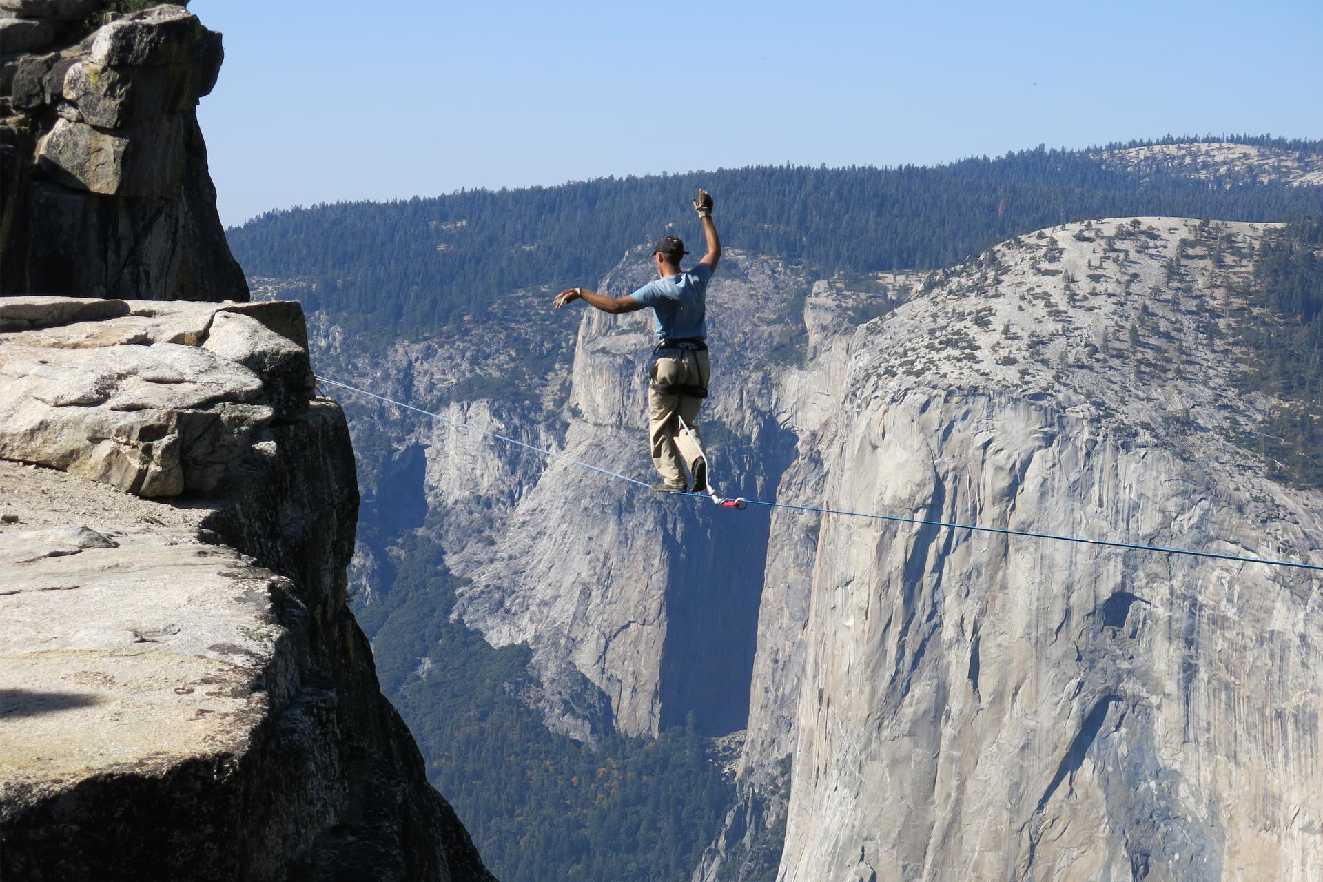 Fotografia przedstawia człowieka, idącego po linie nad przepaścią wgórach. Przy pomocy uniesionych rąk człowiek utrzymuje równowagę. Ma też linę zabezpieczającą.