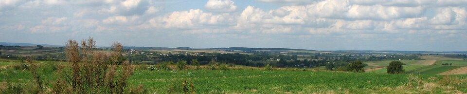 Na zdjęciu lekko pofałdowane tereny zielone. Woddali zabudowania.