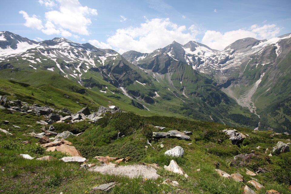 Na zdjęciu teren górzysty, odsłonięte skaliste szczyty pokryte śniegiem, niżej porośnięte trawą.