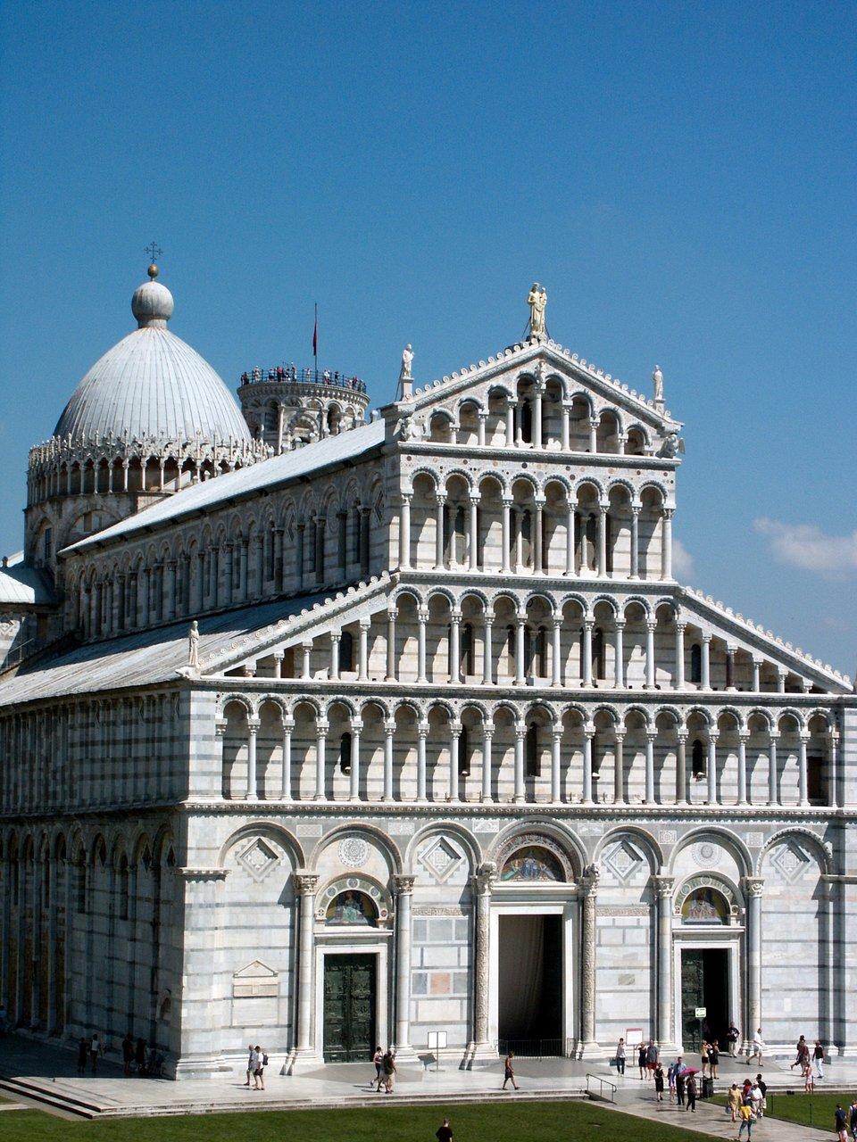 """Widokod strony zachodniej katedry wPizie pw. Santa Maria Assunta (Wniebowzięcia Najświętszej Marii Panny) wzniesionej wlatach 1063-1118-1350. Ztyłu ponad dachem ikopułą widać szczyt dzwonnicy, czyli tzw. """"krzywej wieży"""". Zwróć uwagę, że na jej szczycie widać zwiedzających turystów, co doskonale pokazuje skalę całego założenia architektonicznego.Katedrę – wówczas jeszcze nie ukończoną – poświęcił papież Galezjusz II w1118 r.Dzwonnicę zaczęto wznosić w1174 r., amimo odchylania się od pionu ostatnią kondygnację dodano w1350 r. Ostatecznie osiągnęła wysokość 55 m. Widokod strony zachodniej katedry wPizie pw. Santa Maria Assunta (Wniebowzięcia Najświętszej Marii Panny) wzniesionej wlatach 1063-1118-1350. Ztyłu ponad dachem ikopułą widać szczyt dzwonnicy, czyli tzw. """"krzywej wieży"""". Zwróć uwagę, że na jej szczycie widać zwiedzających turystów, co doskonale pokazuje skalę całego założenia architektonicznego.Katedrę – wówczas jeszcze nie ukończoną – poświęcił papież Galezjusz II w1118 r.Dzwonnicę zaczęto wznosić w1174 r., amimo odchylania się od pionu ostatnią kondygnację dodano w1350 r. Ostatecznie osiągnęła wysokość 55 m. Źródło: Jean-Christophe Benoist, Wikimedia Commons, licencja: CC BY-SA 3.0."""