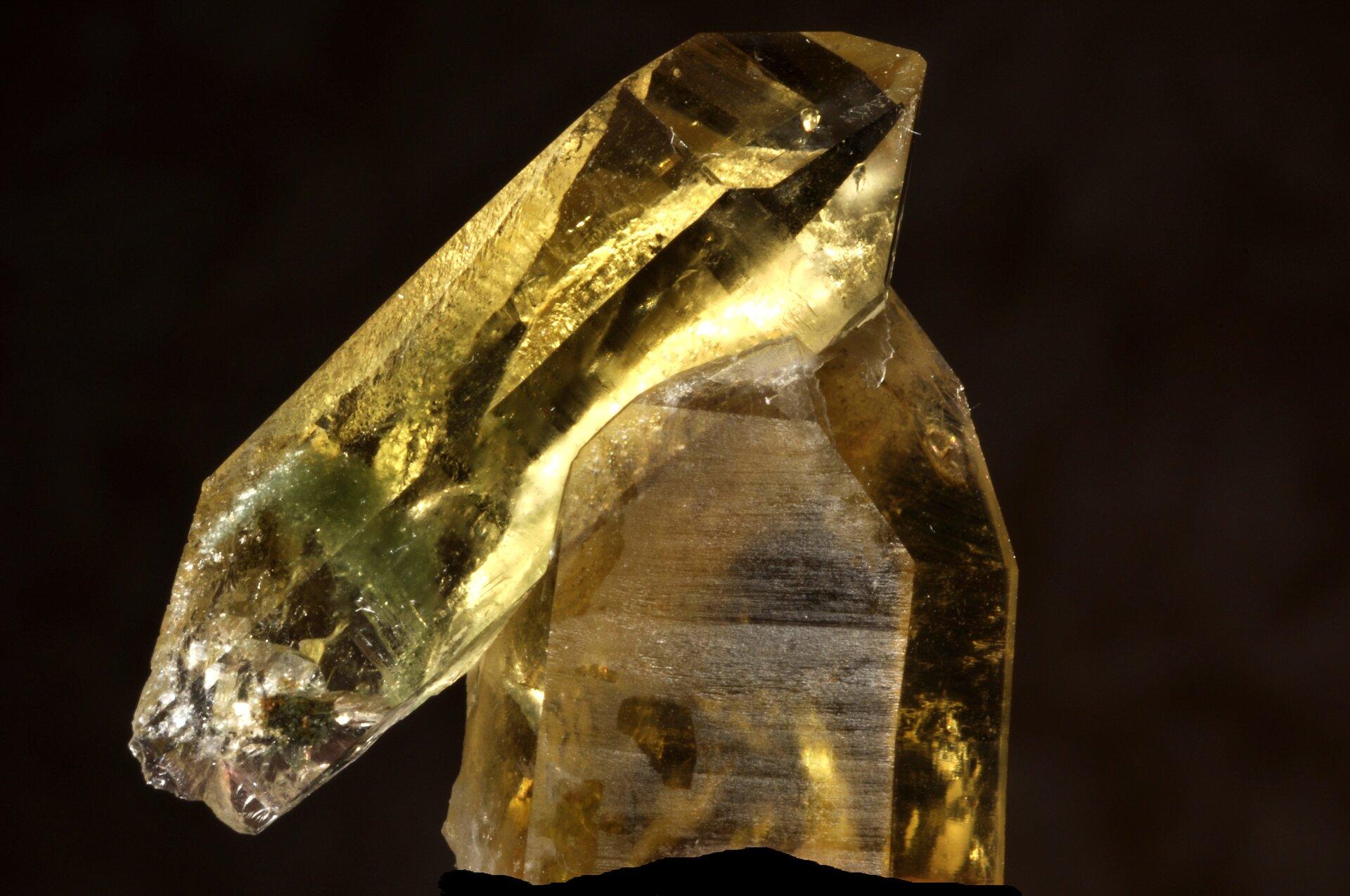 Zdjęcie przedstawia nieoszlifowany kamień szlachetny onazwie cytryn. Barwa żółta, wygląda jakby do jednego kryształu wpionie przyklejono drugi na ukos. Tło zdjęcia czarne, kamień wyraźnie podświetlony zboku.