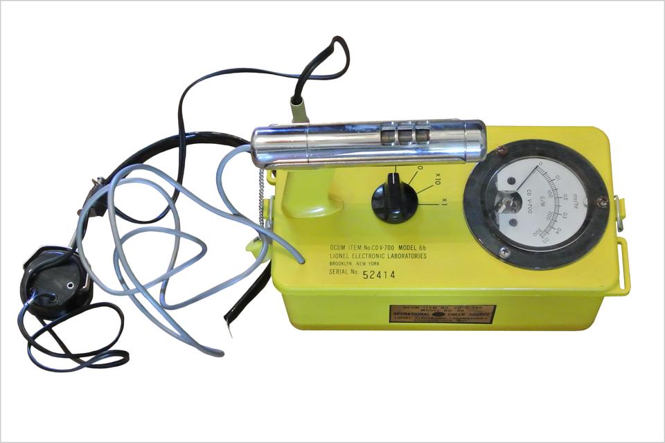Kolorowe zdjęcie przedstawia licznik Geigera. Zdjęcie wykonane zgóry. Po prawej żółte metalowe pudełko. Na górze pudełka znajdują się (od prawej): wskaźnik promieniowania jądrowego ze skalą liczbową, czarne plastikowe pokrętło na środku, po lewej detektor wkształcie rurki. Po lewej stronie zdjęcia kilku kabli iprzewodów. Jeden przewód podłączony jest do obudowy drugi do detektora wkształcie rurki.