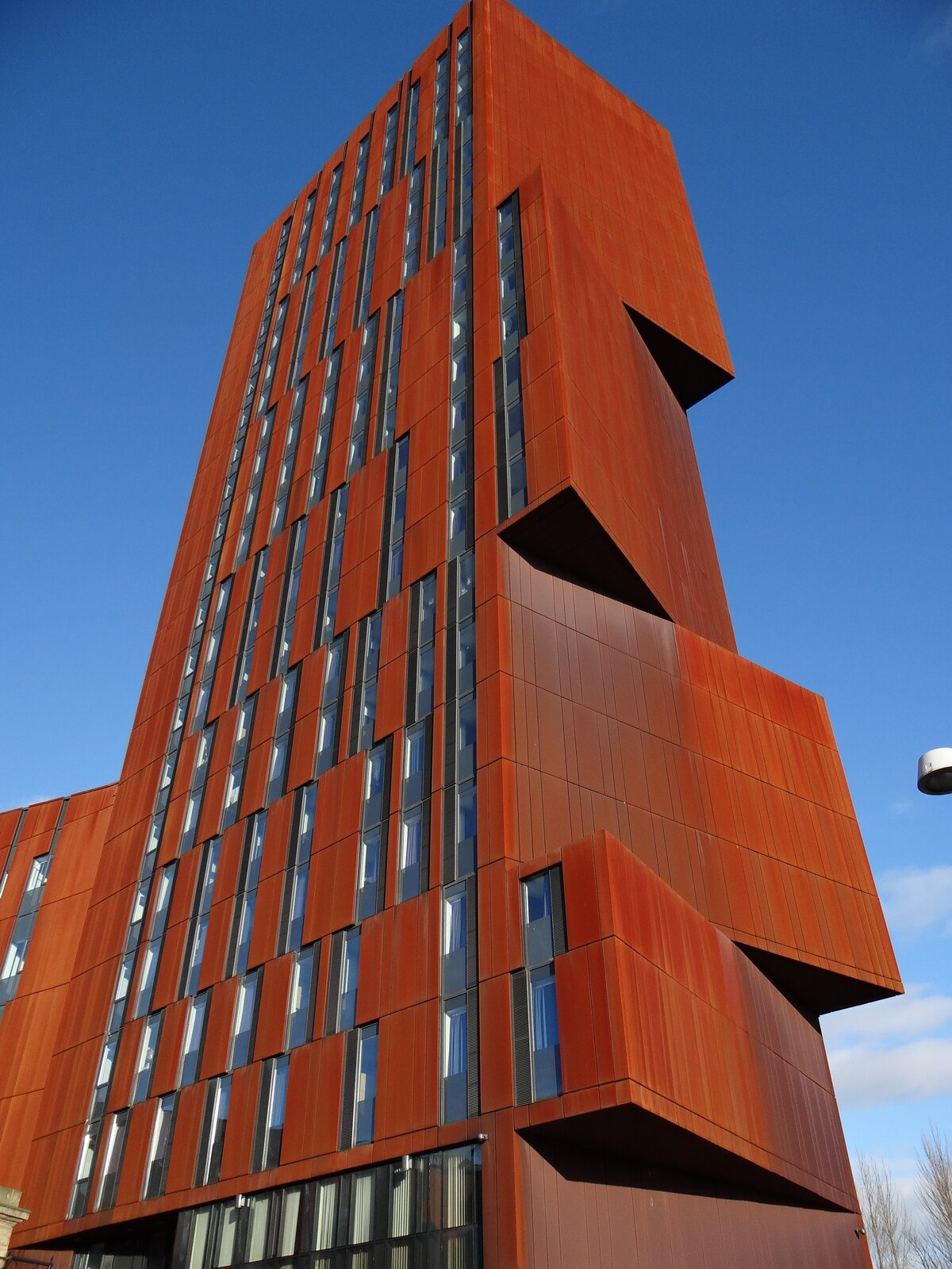 Zdjęcie przedstawia budynek biurowy onieregularnym kształcie, wyglądający jak powstały zułożenia wielkich pudeł jednego na drugim wnie do końca równą wysoką kolumnę. Fasada budynku ma ognistorudy kolor mocno kontrastujący zniebieskim niebem wtle.