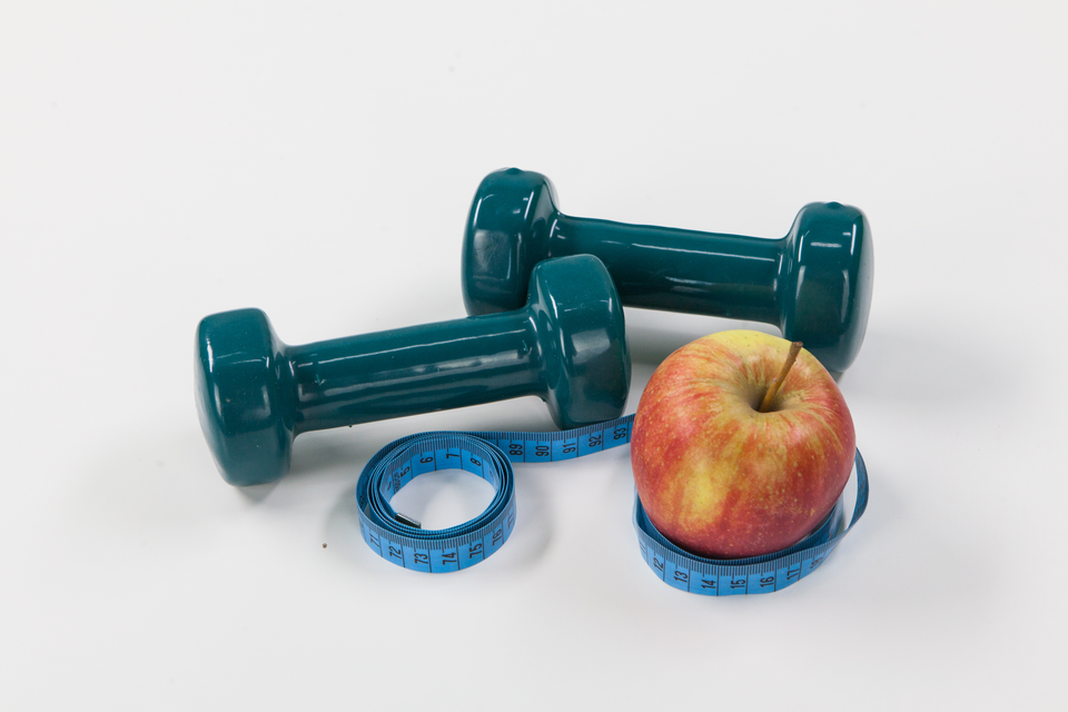 Fotografia przedstawia dwa niebieskie ciężarki do ćwiczeń, błękitny centymetr krawiecki iczerwono – żółte jabłko zogonkiem. Należy zinterpretować tę ilustrację.