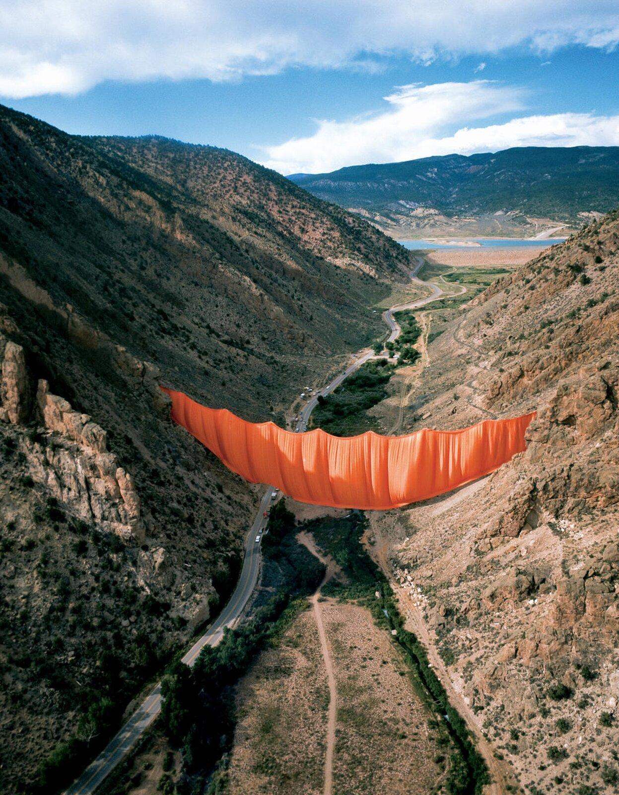 Ilustracja przedstawia czerwony materiał zawieszony pomiędzy dwoma zboczami wzgórz. Artyści na 28 godzin przegrodzili Wielki Kanion Kolorado pomarańczową kurtyną wysokości 42 metrów.