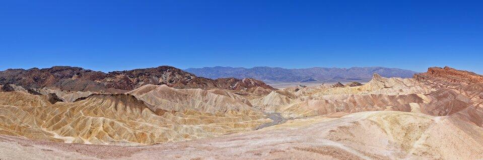 Na pierwszym planie rozległa dolina pozbawiona roślinności. Dolinę otaczają potężne pasma górskie. Wtle kolejne pasma górskie. Bezchmurne niebo.