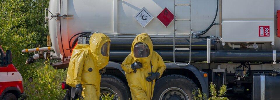 Kolorowe zdjęcie przedstawia dwójkę ludzi ubranych wżółte kombinezony ochronne. Mają założone maski przeciwgazowe. Za nimi stoi biała cysterna na tle zielonych drzew. Na cysternie biały iczerwony kwadrat wskazujący na przewożenie substancji toksycznych.