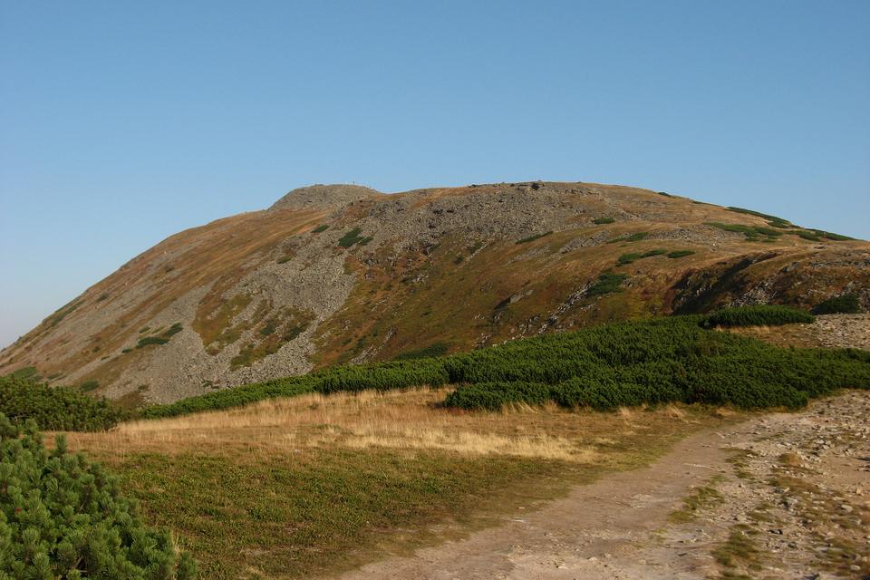 Fotografia prezentuje wysoką górę ołagodnym szczycie, na którą prowadzi szlak turystyczny rozpoczynający się po prawej stronie zdjęcia.