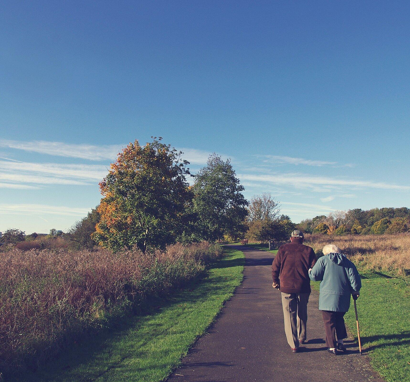 Na zdjęciu para starszych osób idzie ścieżką wśród zieleni. Kobieta podpiera się laską.